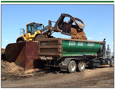 Excavation Machinery Dumping Dirt Into Dumpster